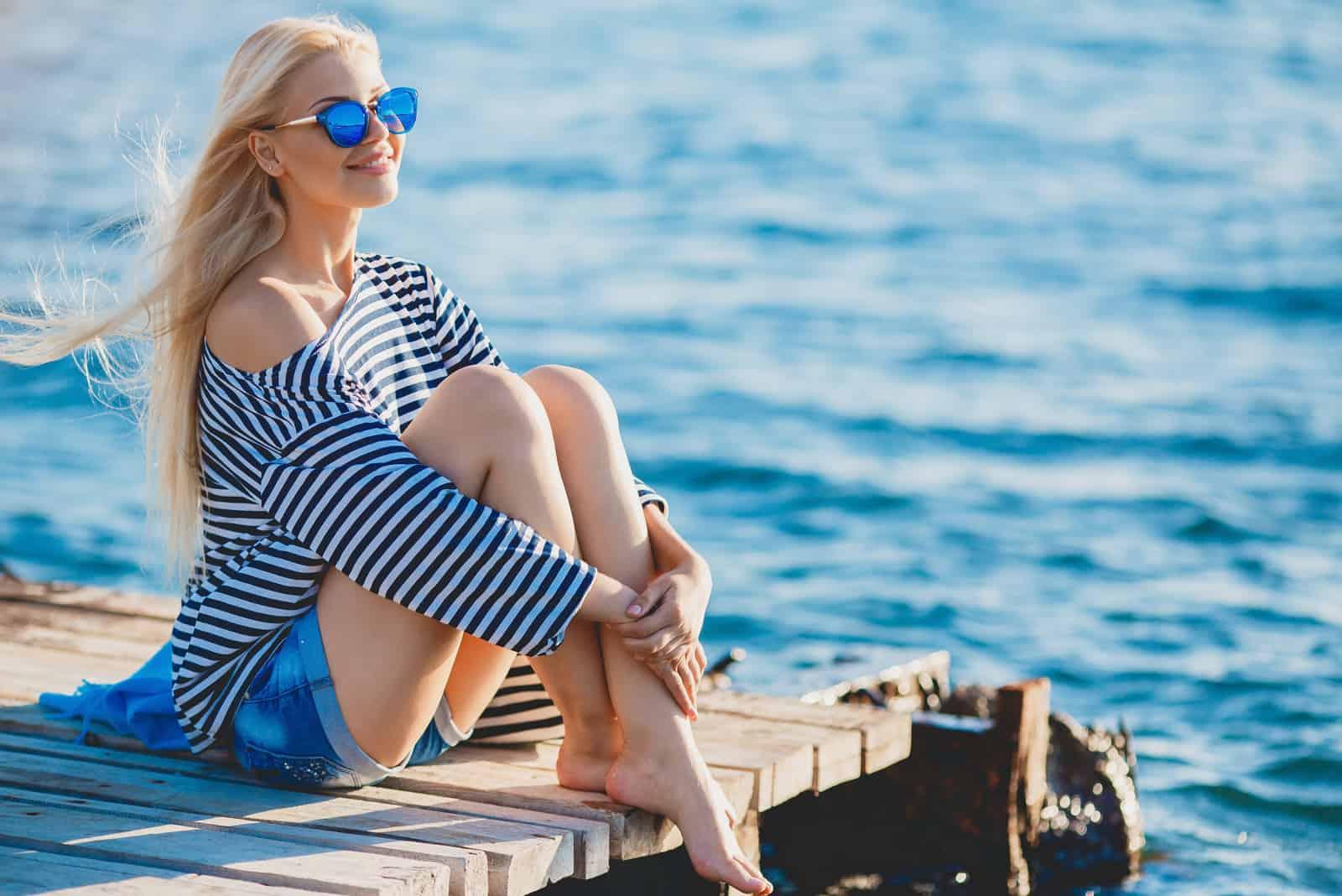 une belle femme aux longs cheveux blonds est assise sur la jetée