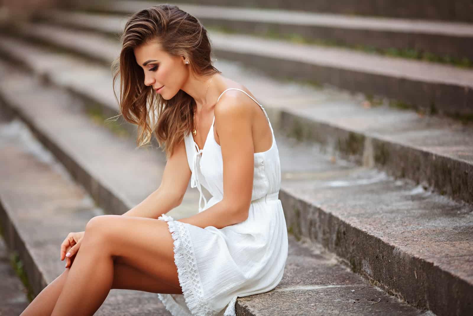 une belle femme dans une robe blanche est assise sur les marches avec ses yeux baissés