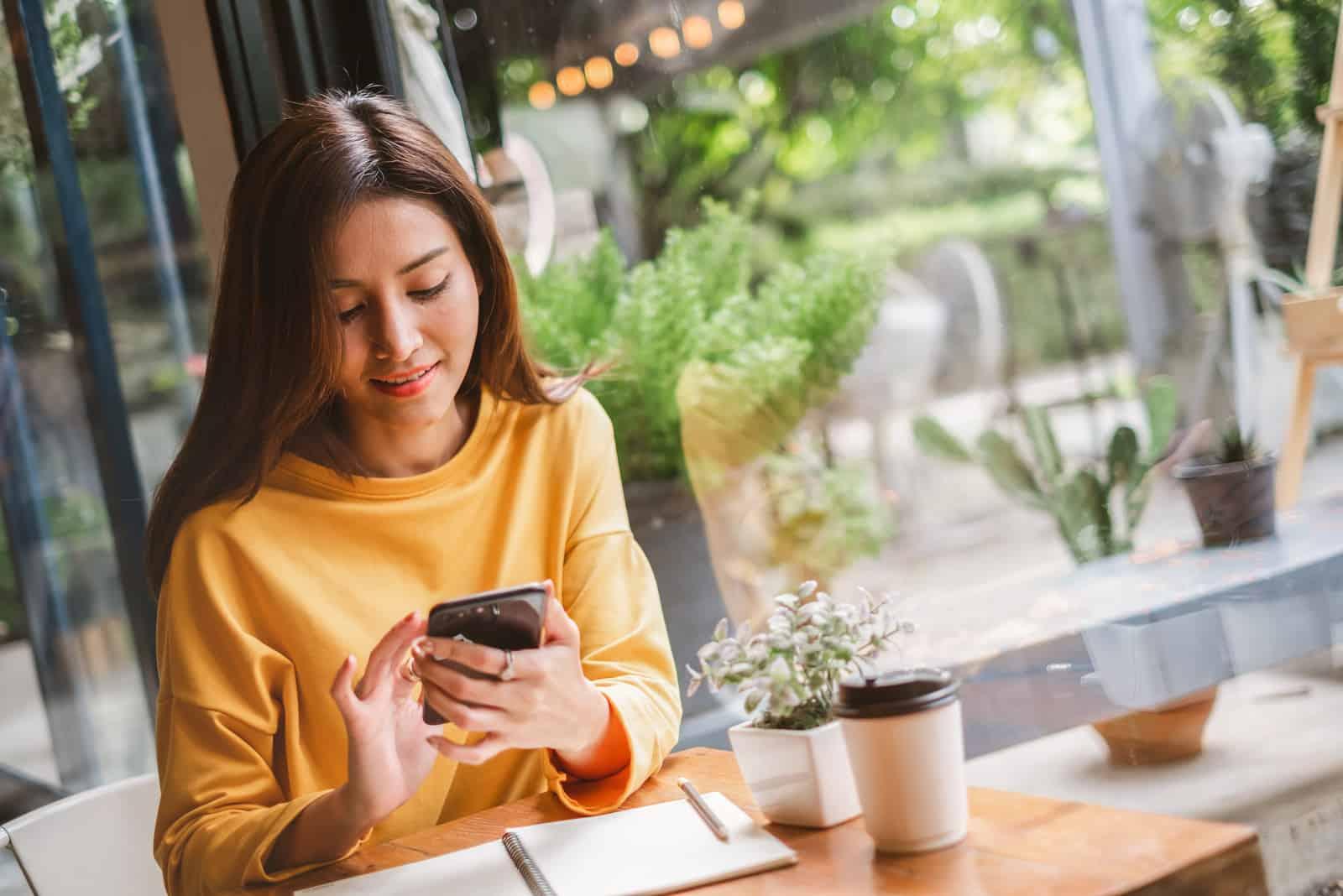 une femme assise dans un café et en appuyant sur un téléphone