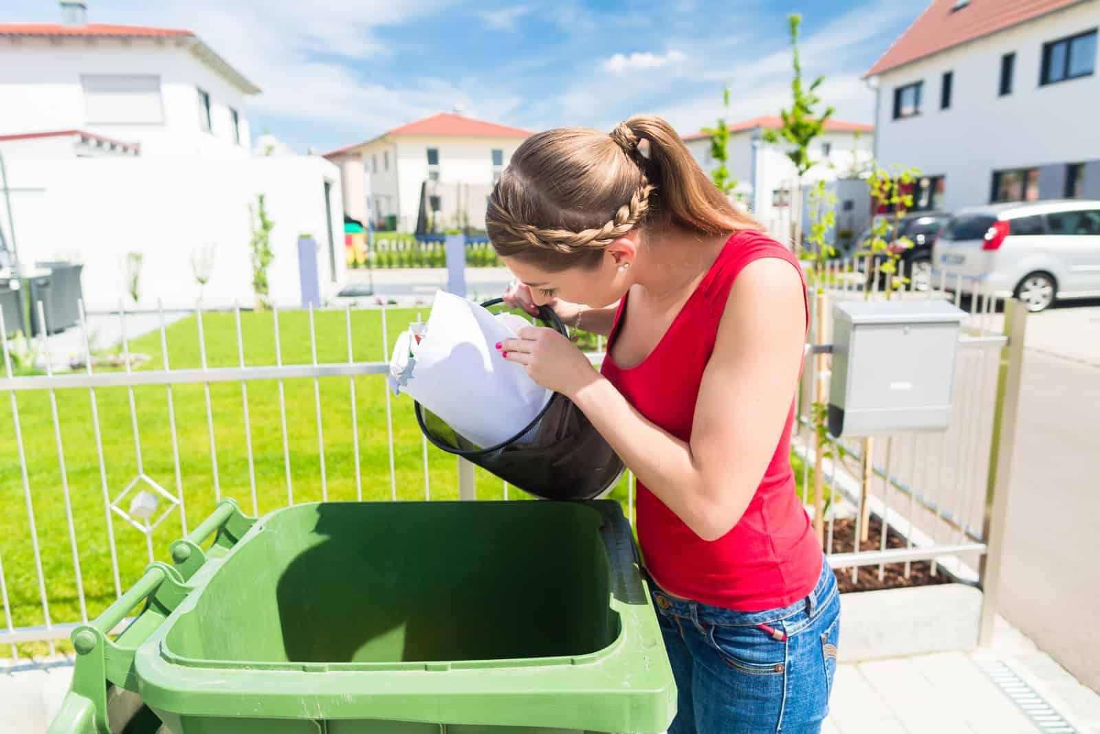 une femme aux cheveux attachés jette des ordures