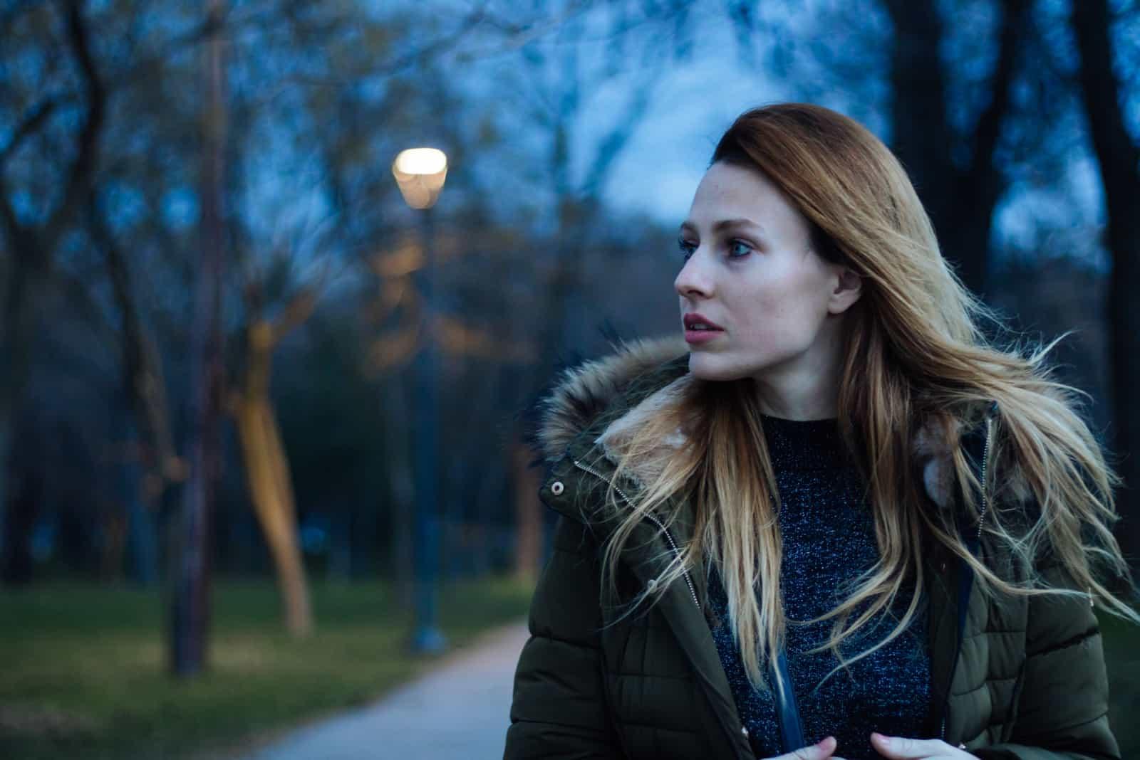 une femme aux longs cheveux blonds marche dans la rue