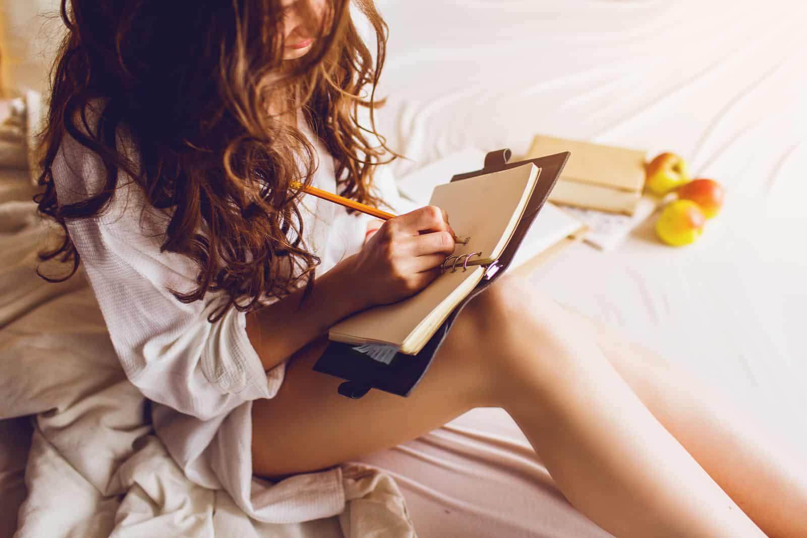 une femme aux longs cheveux bruns est assise et écrit un journal