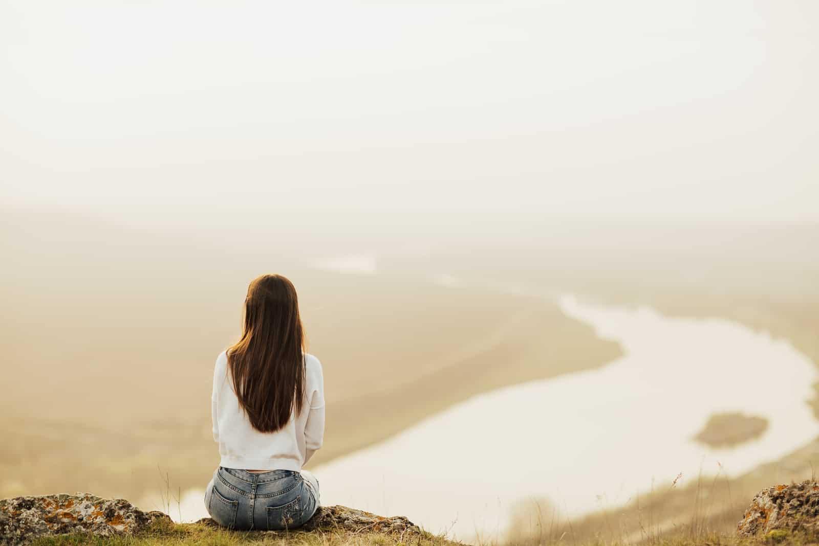 une femme aux longs cheveux noirs est assise sur un rocher