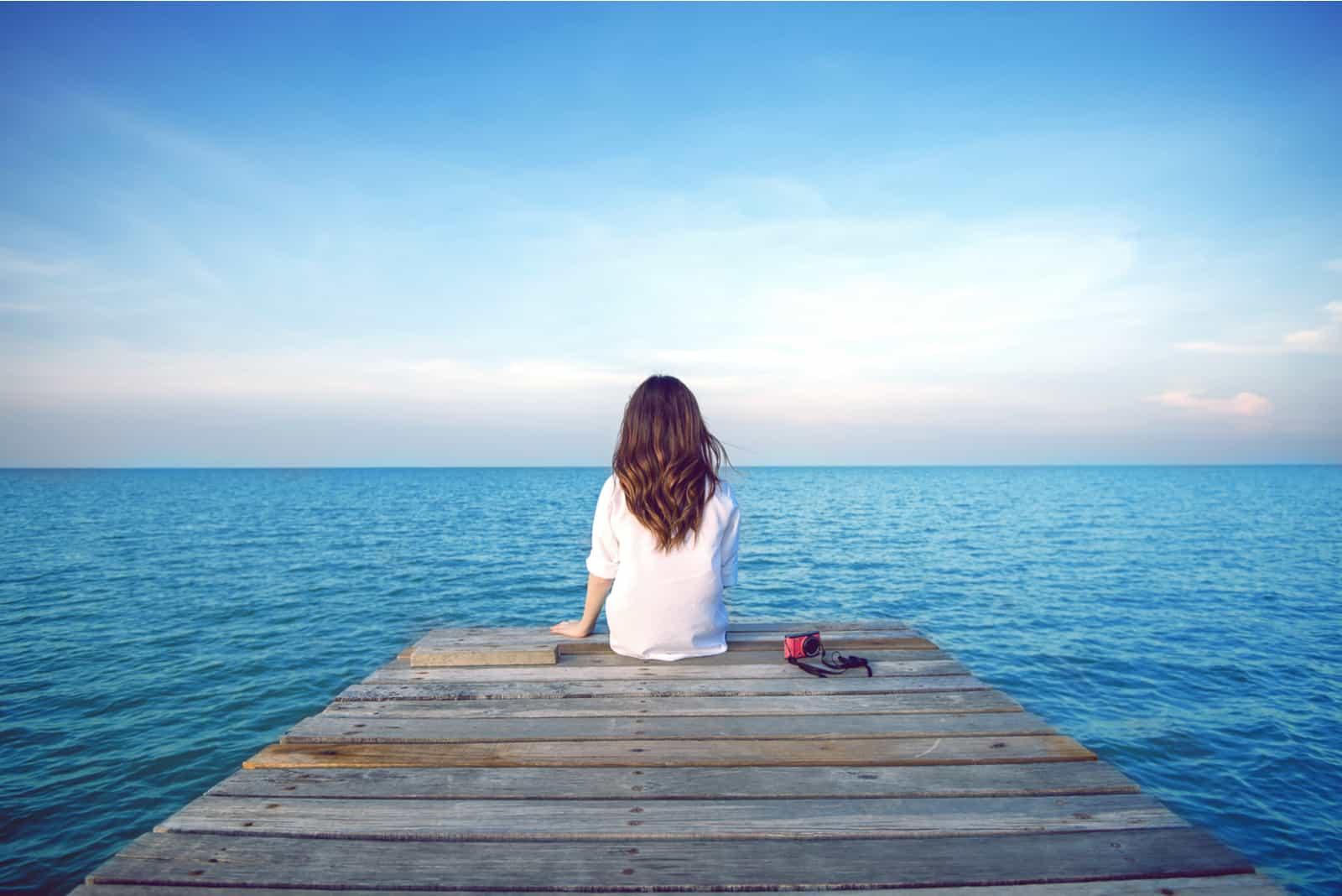 une femme aux longs cheveux noirs est assise sur une jetée