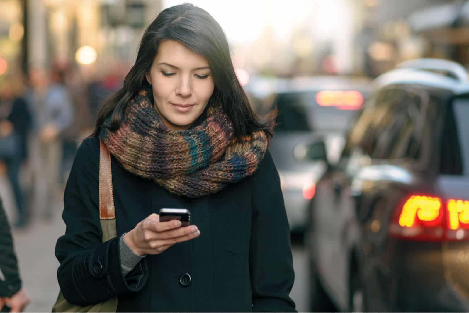 une femme aux longs cheveux noirs se dresse dans la rue et un bouton sur le téléphone