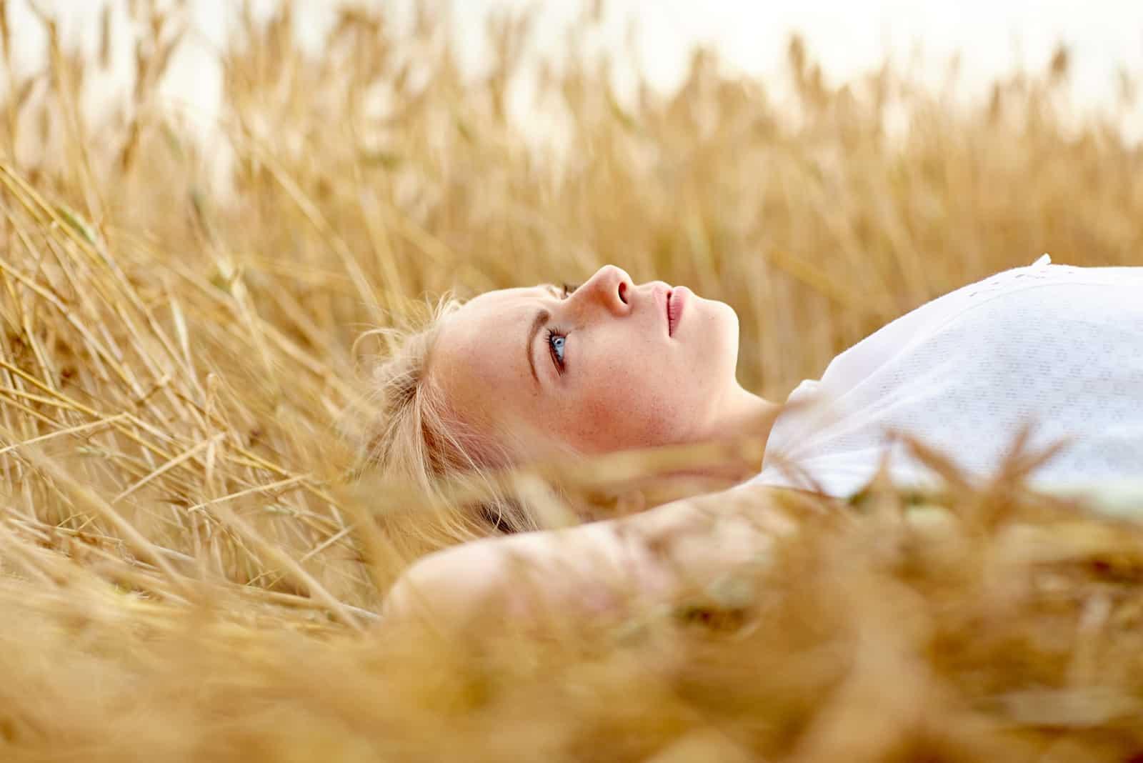 une femme blonde allongée sur l'herbe