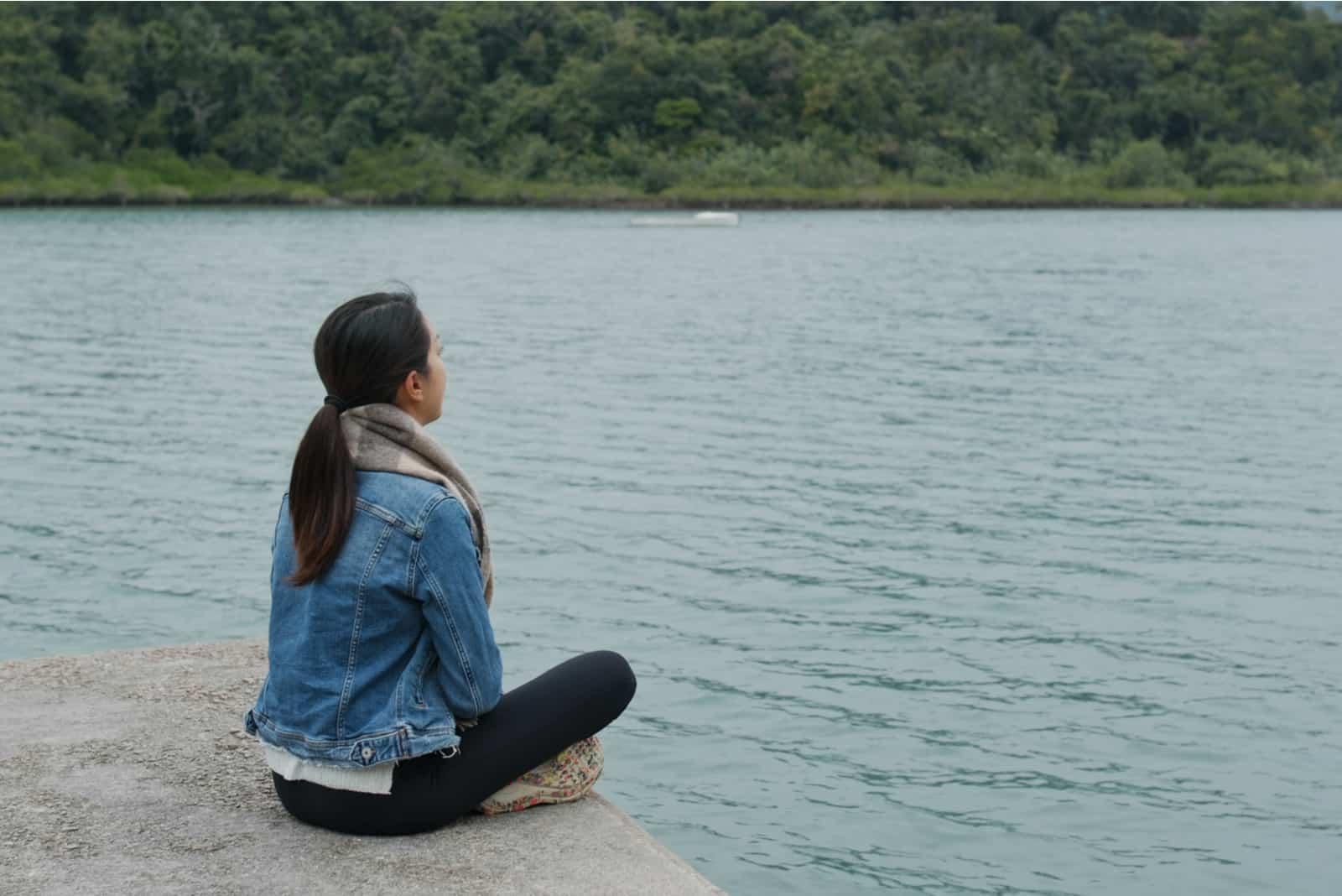 une femme est assise à côté d'une jetée et donne sur la mer
