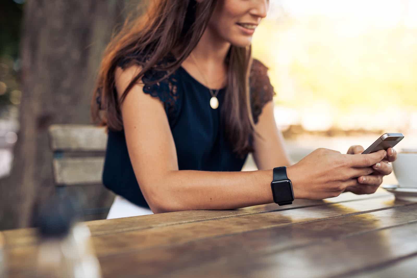 une femme est assise à une table et une clé sur le téléphone