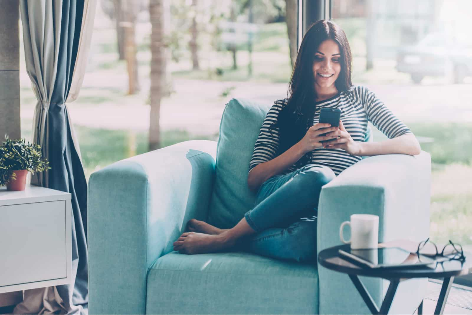 une femme est assise dans un fauteuil et un bouton sur le téléphone