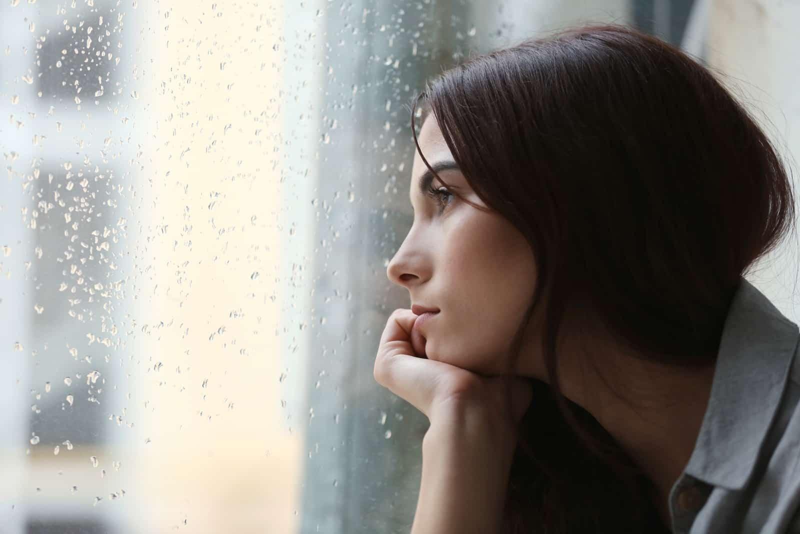 une femme imaginaire aux longs cheveux noirs regarde par la fenêtre