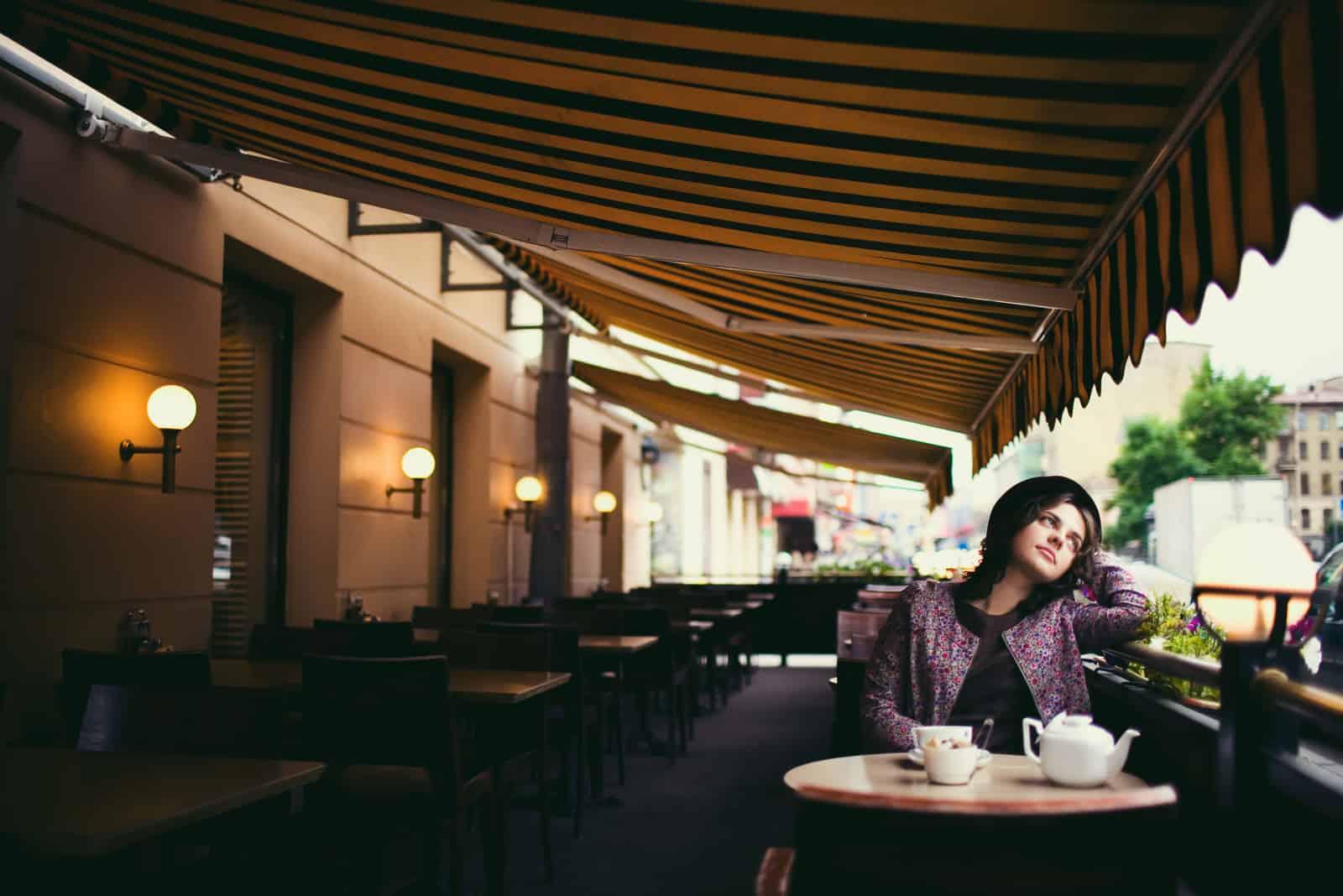 une femme imaginaire avec un chapeau sur la tête est assise à une table