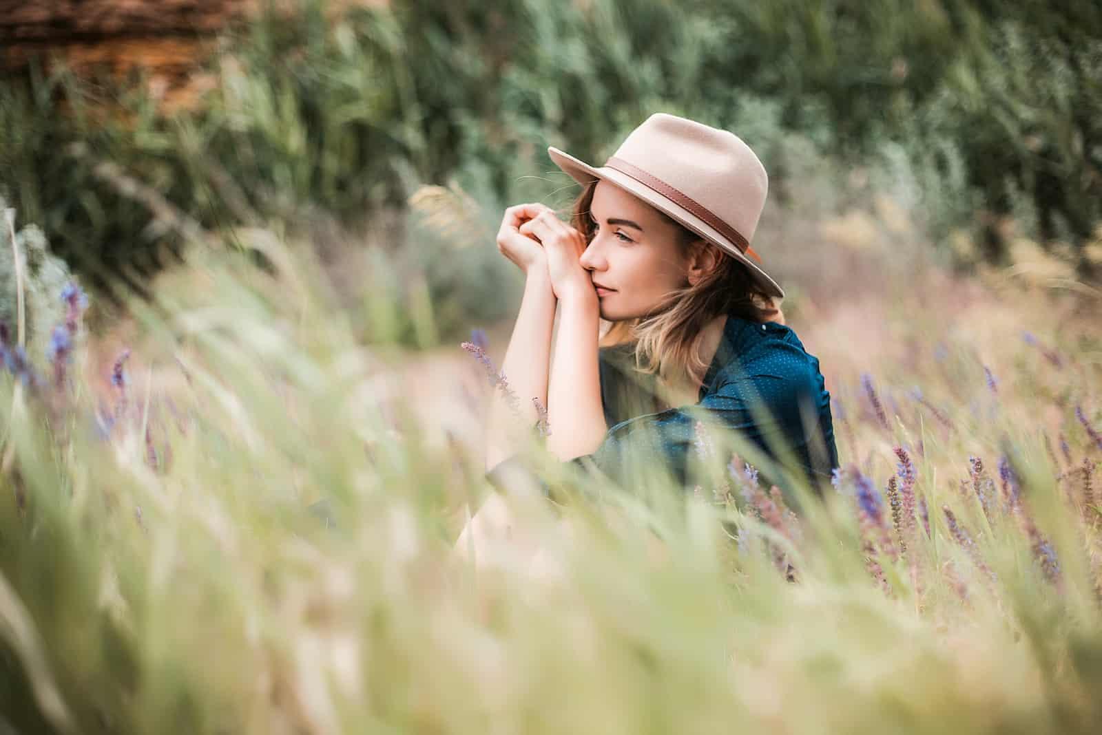 une femme imaginaire avec un chapeau sur la tête est assise dans l'herbe