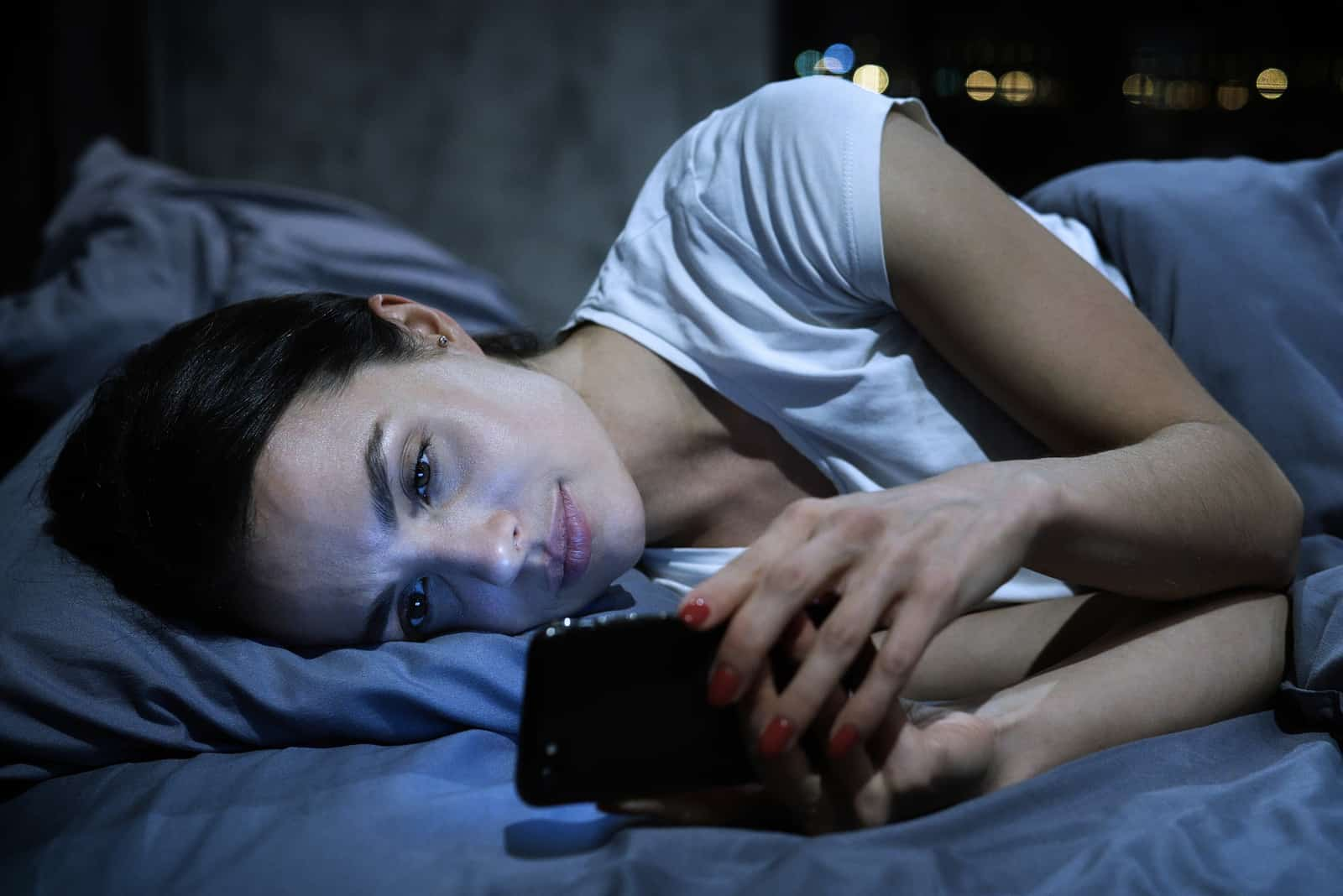 une femme imaginaire couchée dans son lit et en appuyant sur un téléphone