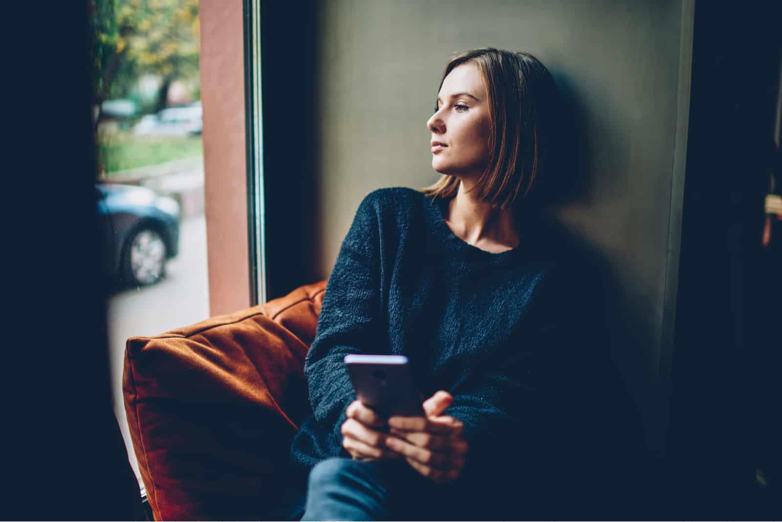 une femme imaginaire est assise avec un téléphone à la main et regarde au loin
