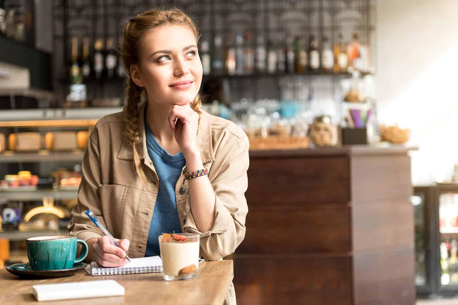une femme imaginaire est assise dans un café et écrit