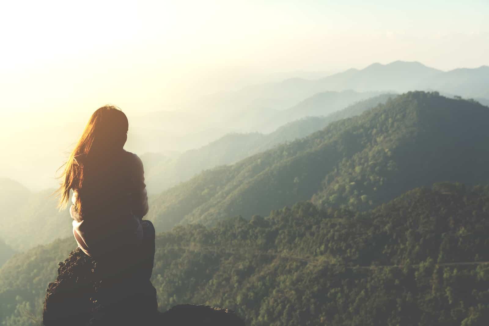 une femme imaginaire est assise sur une pierre, le dos tourné