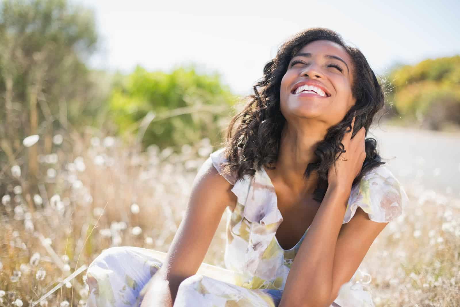 une femme noire souriante est assise dans l'herbe