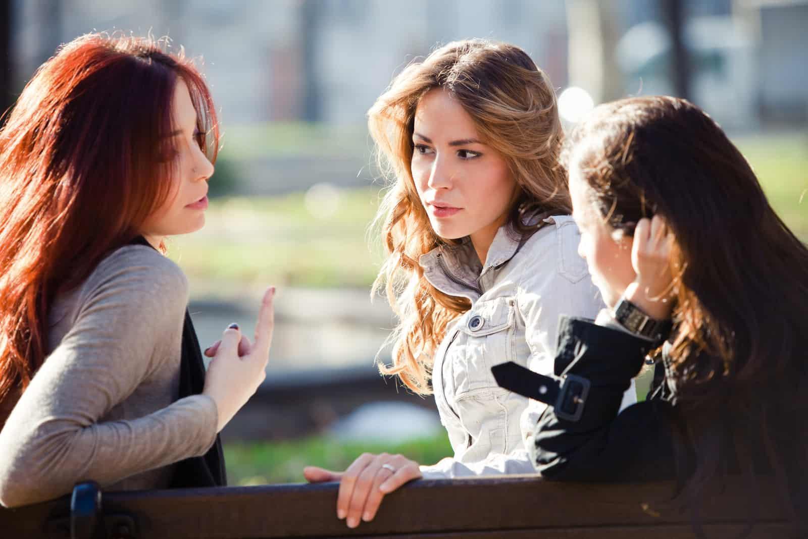 une femme parle à des amis assis sur un banc