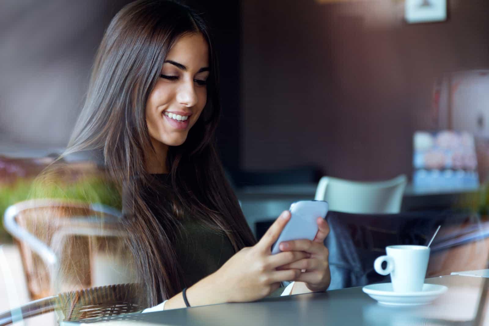une femme souriante assise dans un café et en tapant au téléphone
