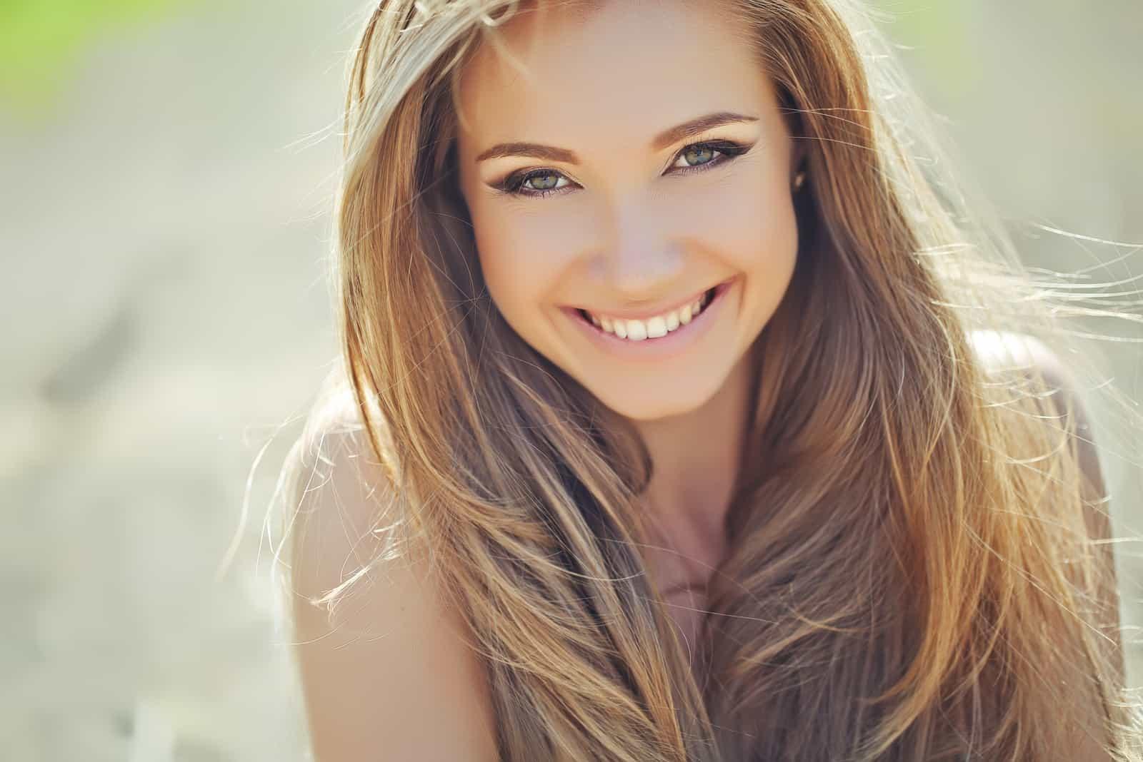 une femme souriante aux longs cheveux bruns