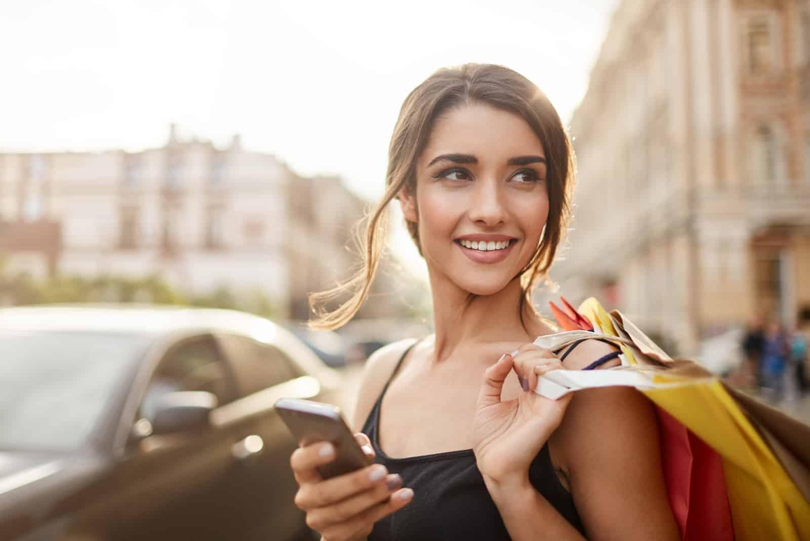 une femme souriante avec des sacs à la main