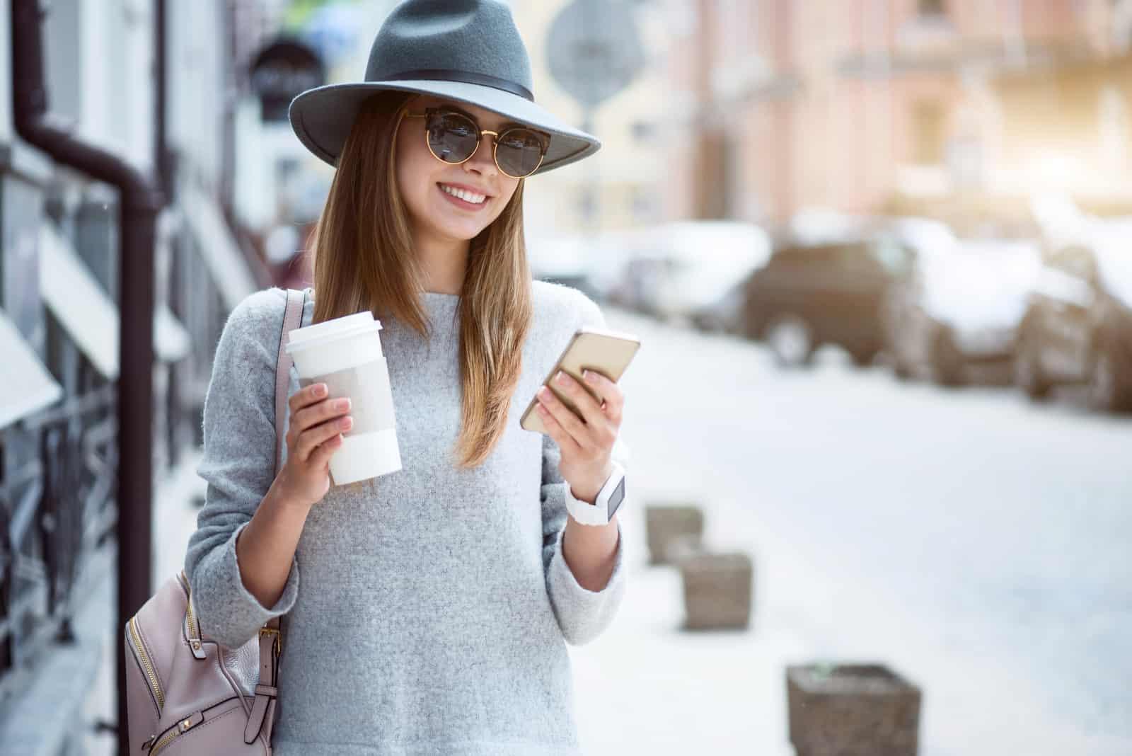 une femme souriante avec un chapeau sur sa tête se dresse et un bouton sur le téléphone