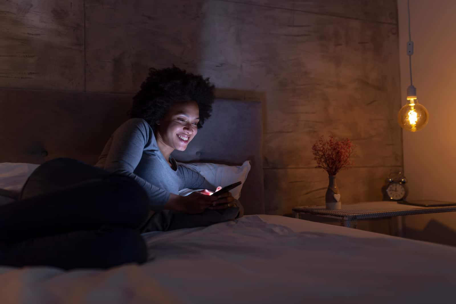 une femme souriante couchée dans son lit et en appuyant sur un téléphone