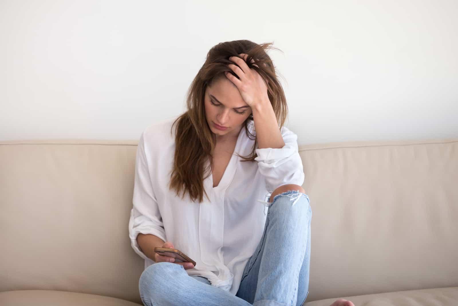 une femme triste est assise sur le canapé et tient le téléphone dans sa main