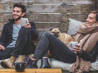 homme et femme souriant assis près du mur en bois