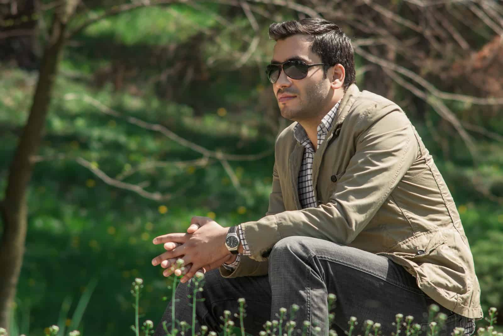 Bel homme assis dans un parc