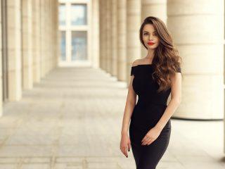 une belle femme aux longs cheveux noirs dans une robe noire se dresse