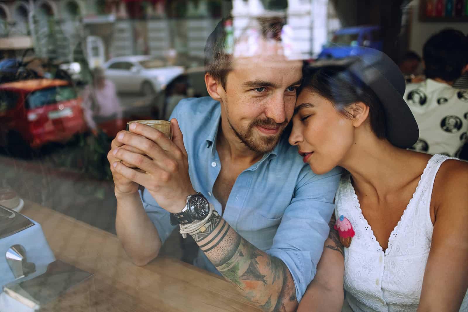 Couple de rêve au repos dans un café derrière la fenêtre à la journée ensoleillée