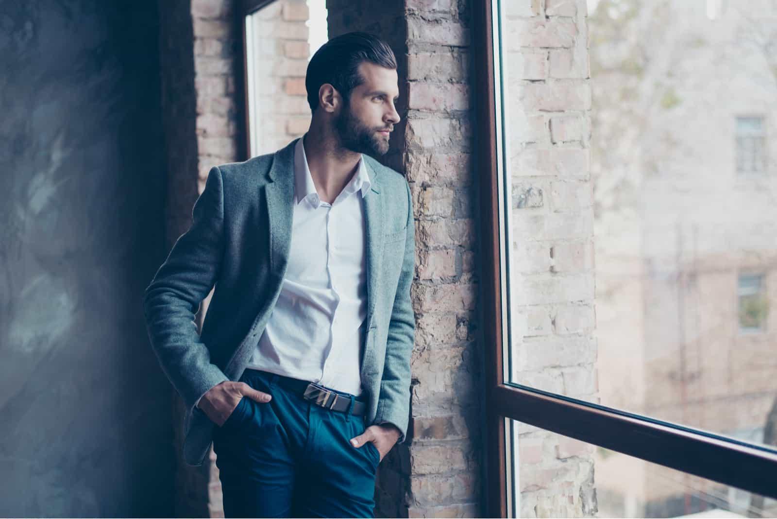 Élégant jeune homme barbu se tient près de la fenêtre