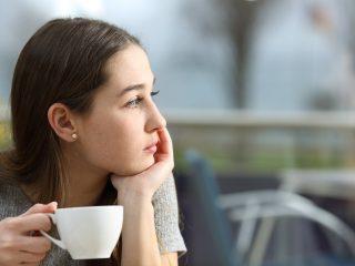 femme tenant une tasse de café à l'écart
