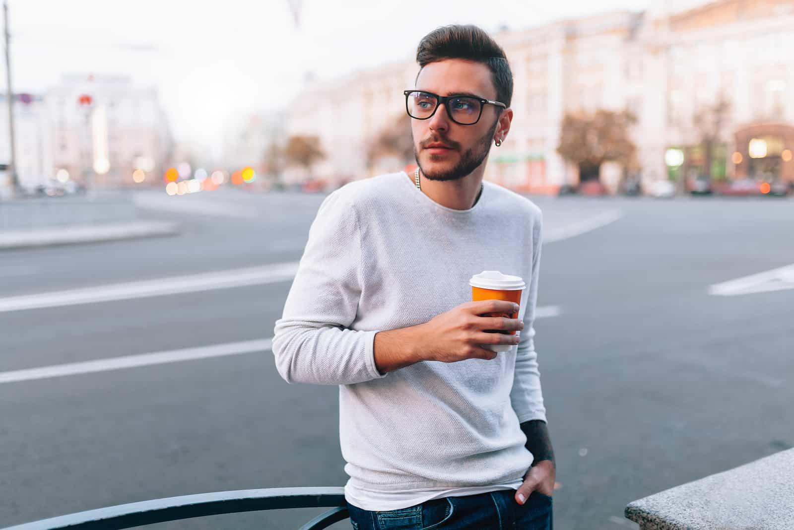 Homme de hipster debout avec du café à emporter