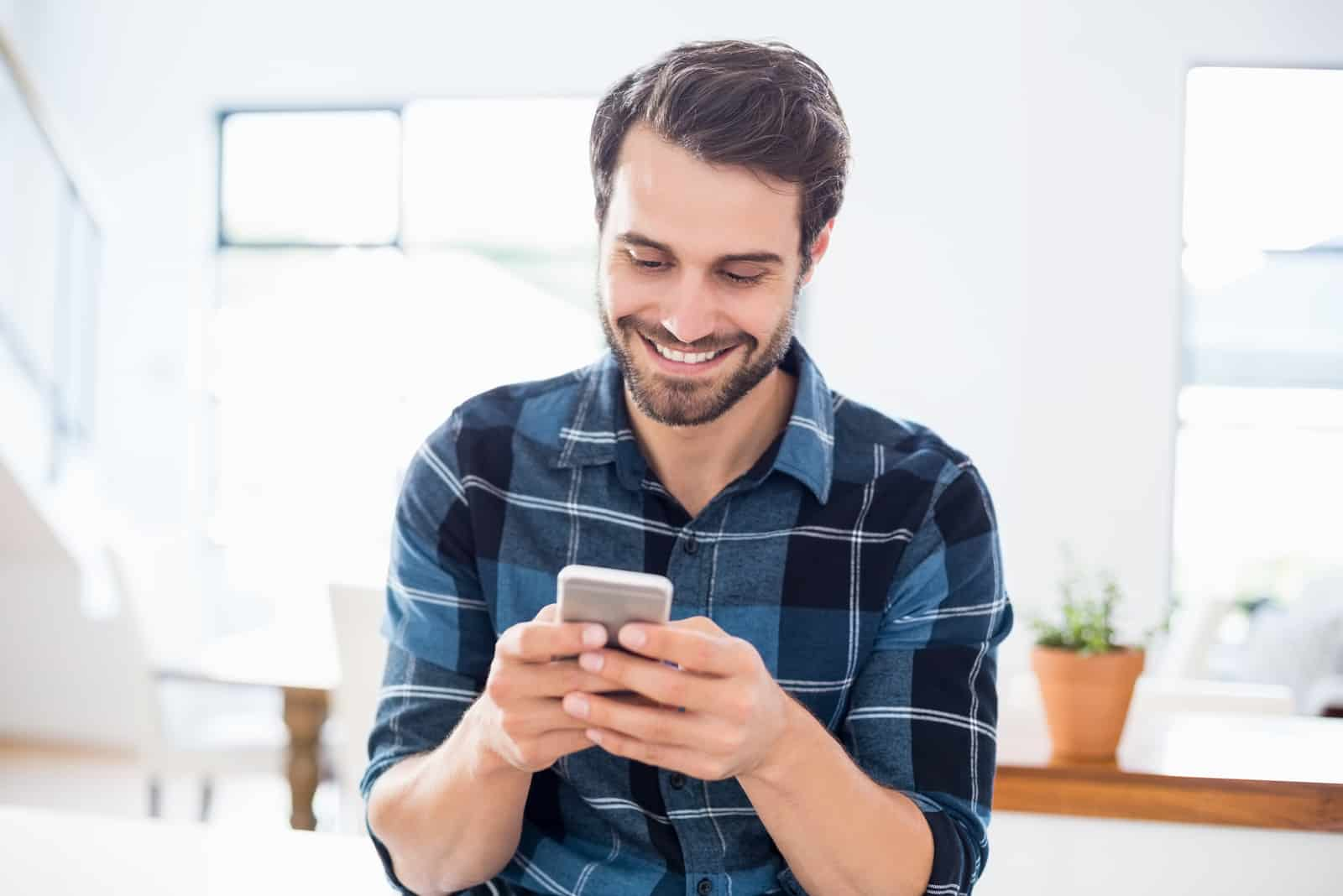 Homme souriant utilisant son téléphone