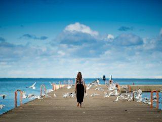 femme debout sur un quai entouré d'oiseaux