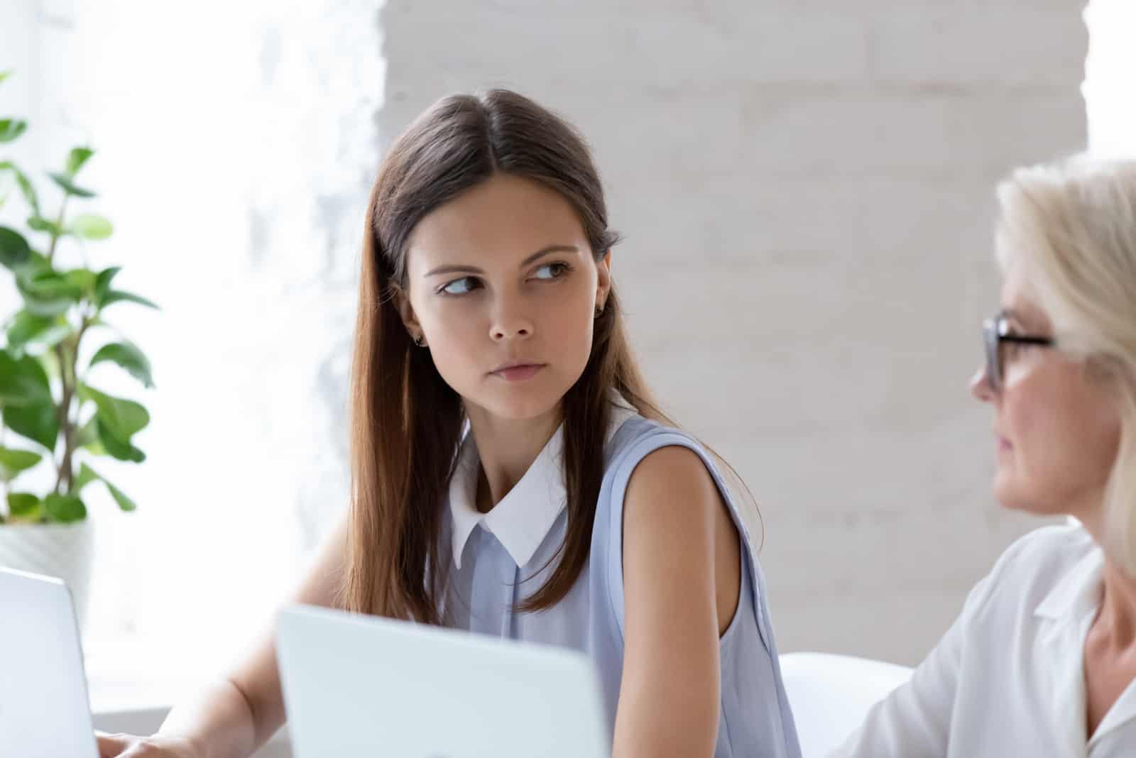 Travailleuse millénaire sérieuse, assise à son bureau, regardant en colère un collègue plus âgé.
