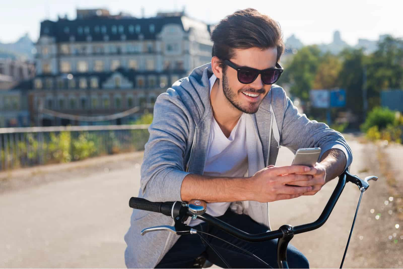 Un homme souriant avec des lunettes sur la tête se tient appuyé sur son vélo et un bouton sur le téléphone