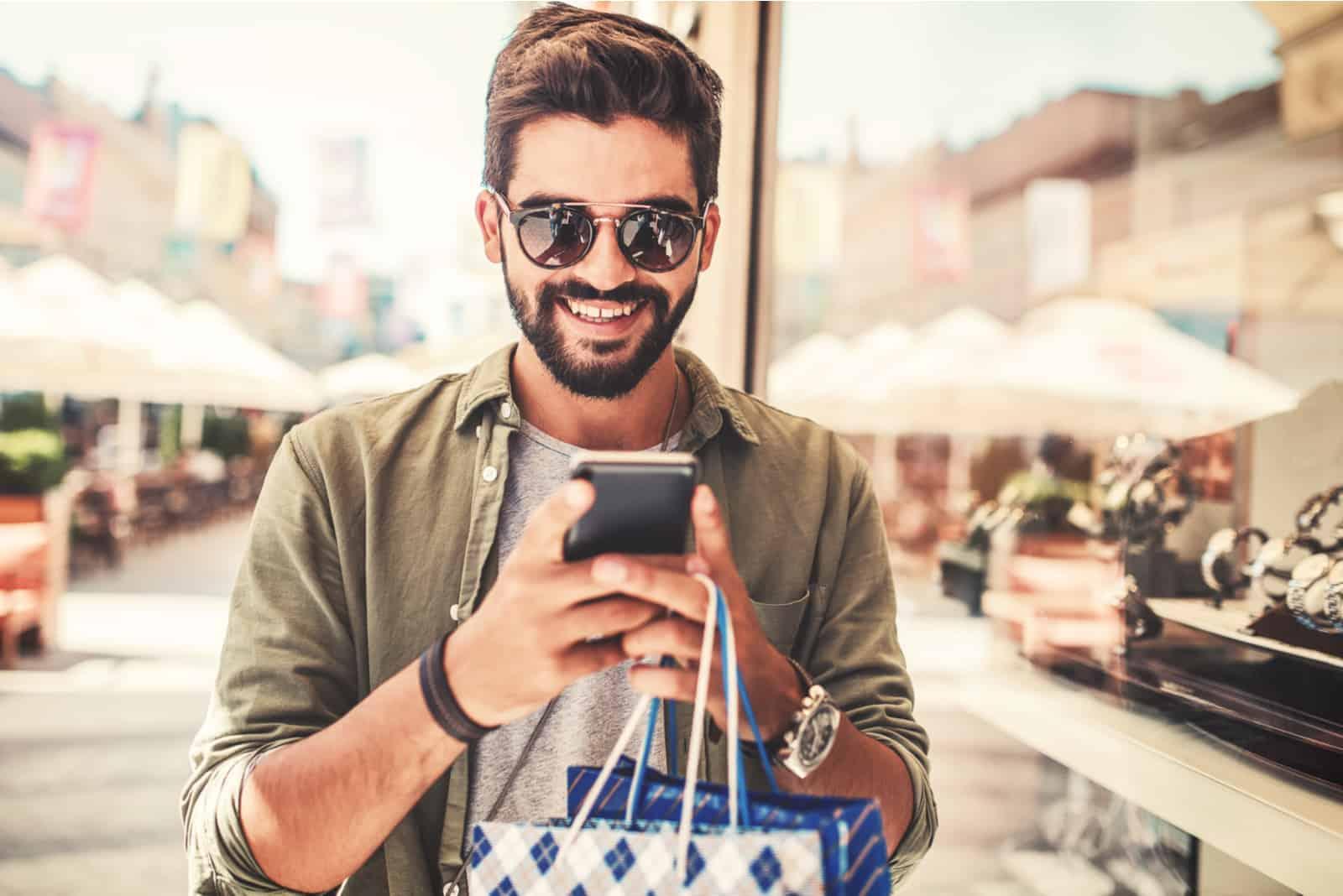 Un homme souriant avec des sacs à la main se dresse dans la rue et les touches du téléphone