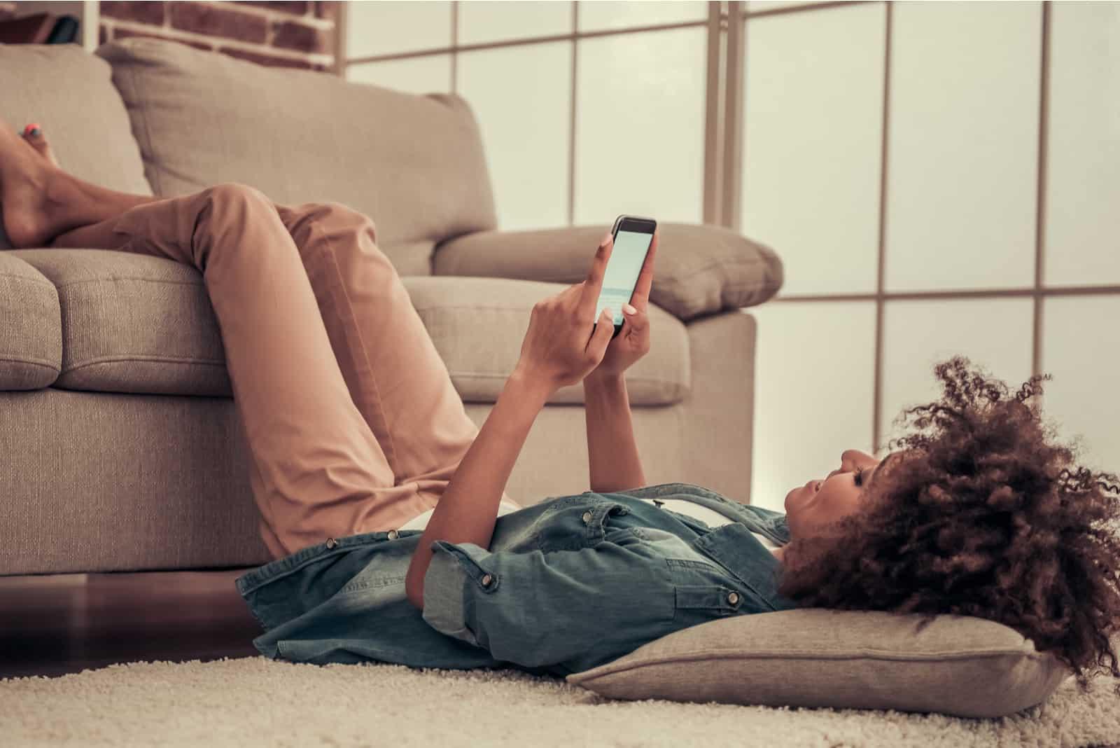 Une femme aux cheveux crépus se trouve sur le sol et tient le téléphone dans sa main