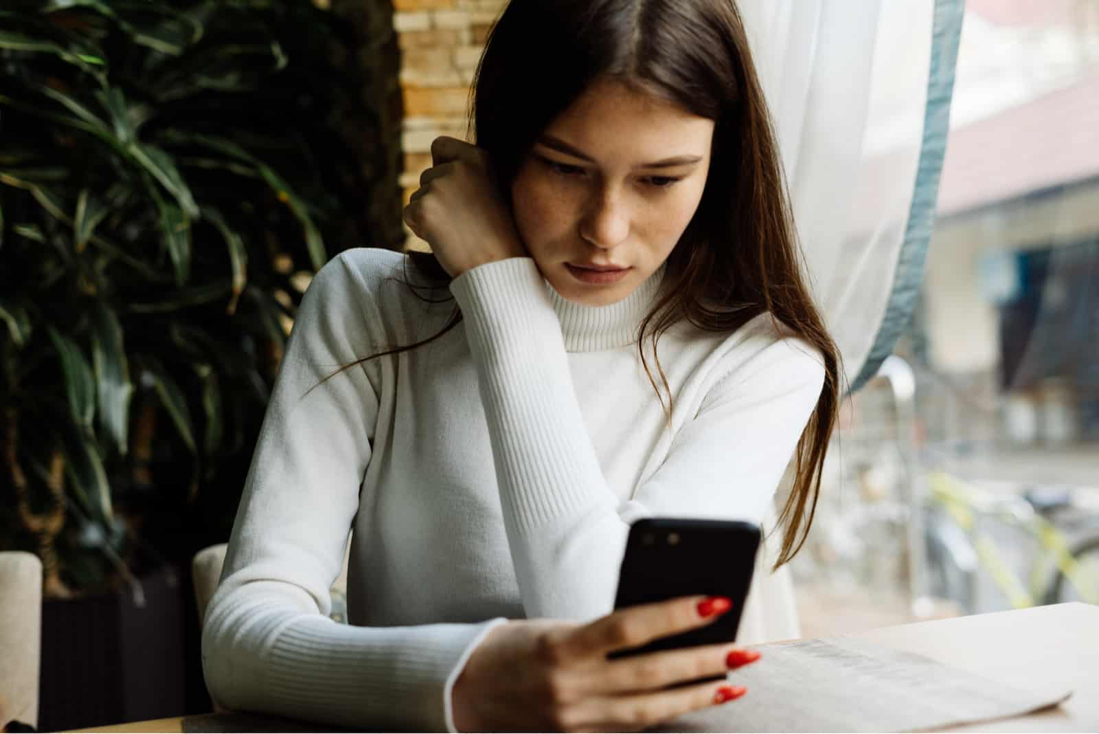 Une femme triste est assise à une table tenant un téléphone à la main