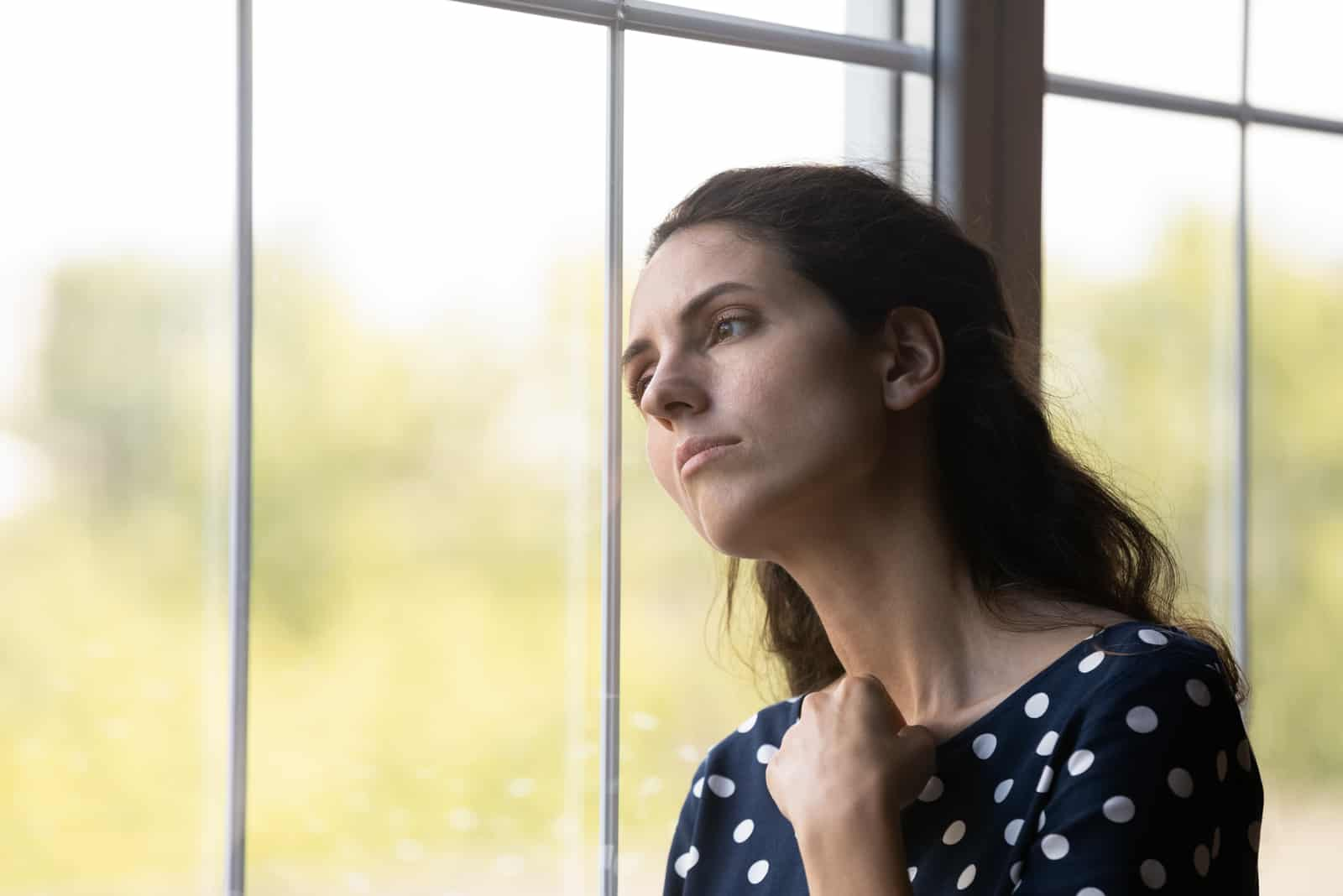 Ung femme de race blanche regarder à distance de la fenêtre