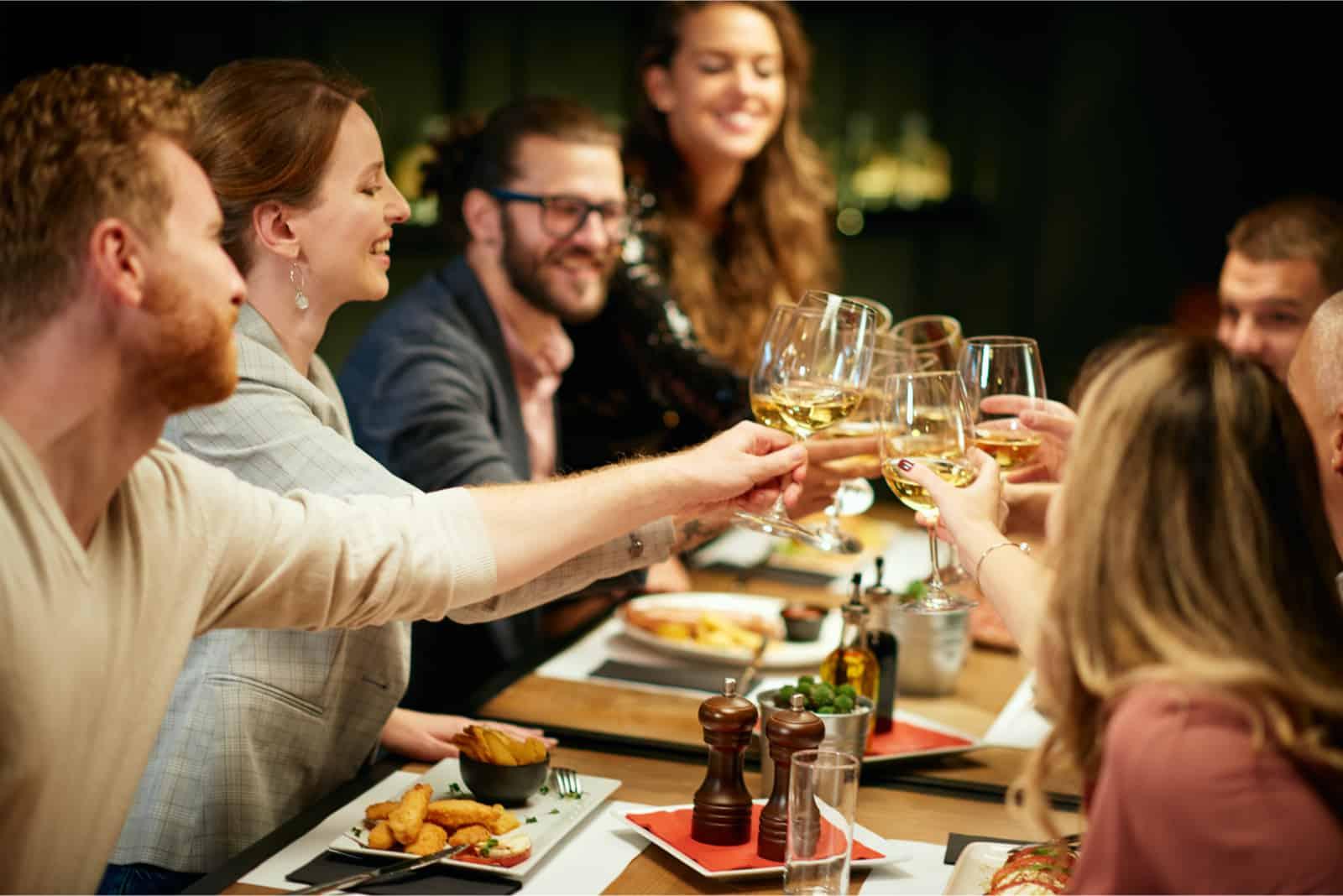 amis en train de griller avec du vin en dînant