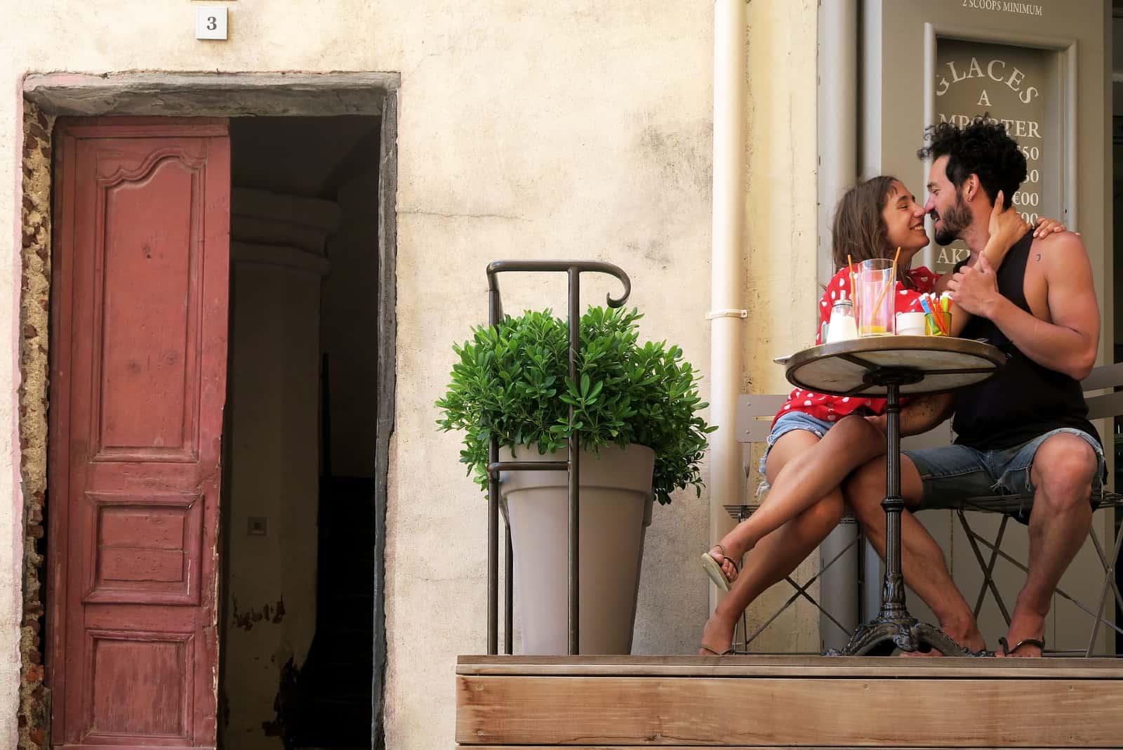 homme et femme sur le point de s'embrasser assis à table