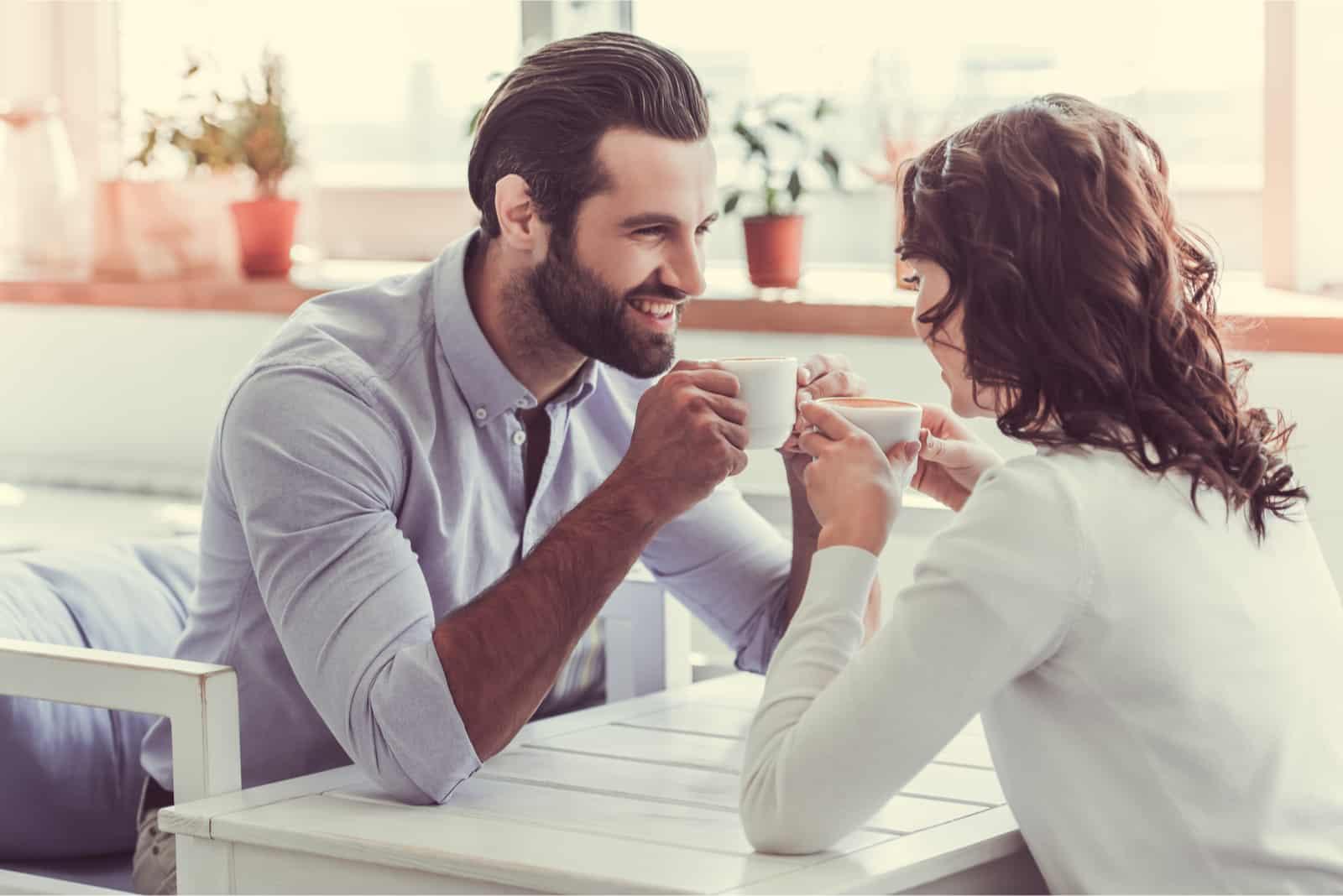 homme et femme prenant un café assis au café