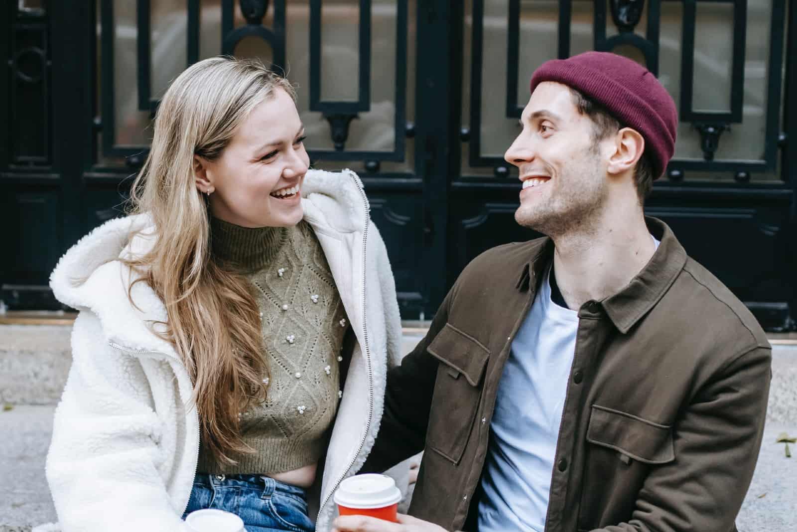 homme et femme souriant assis sur les escaliers