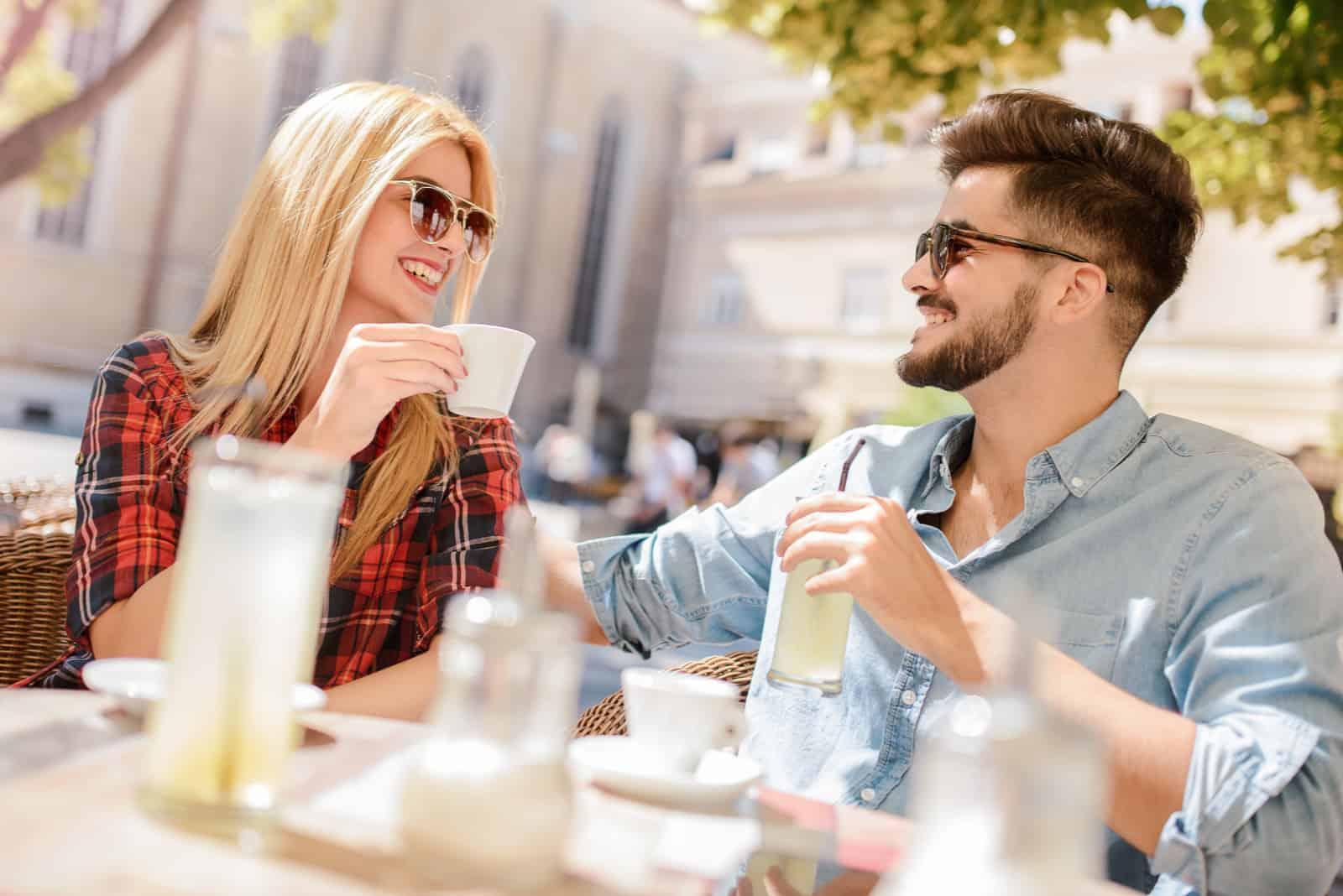 homme et femme buvant du café assis en plein air