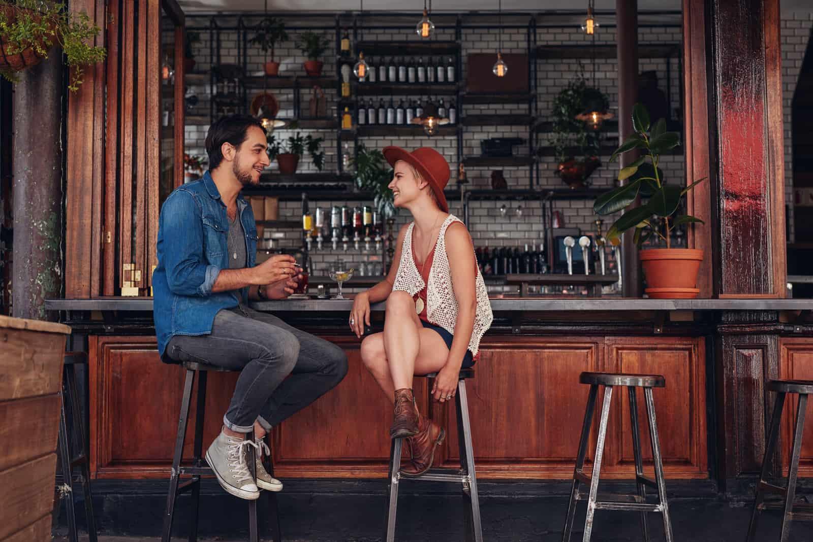 homme et femme parlant assis sur des chaises de bar