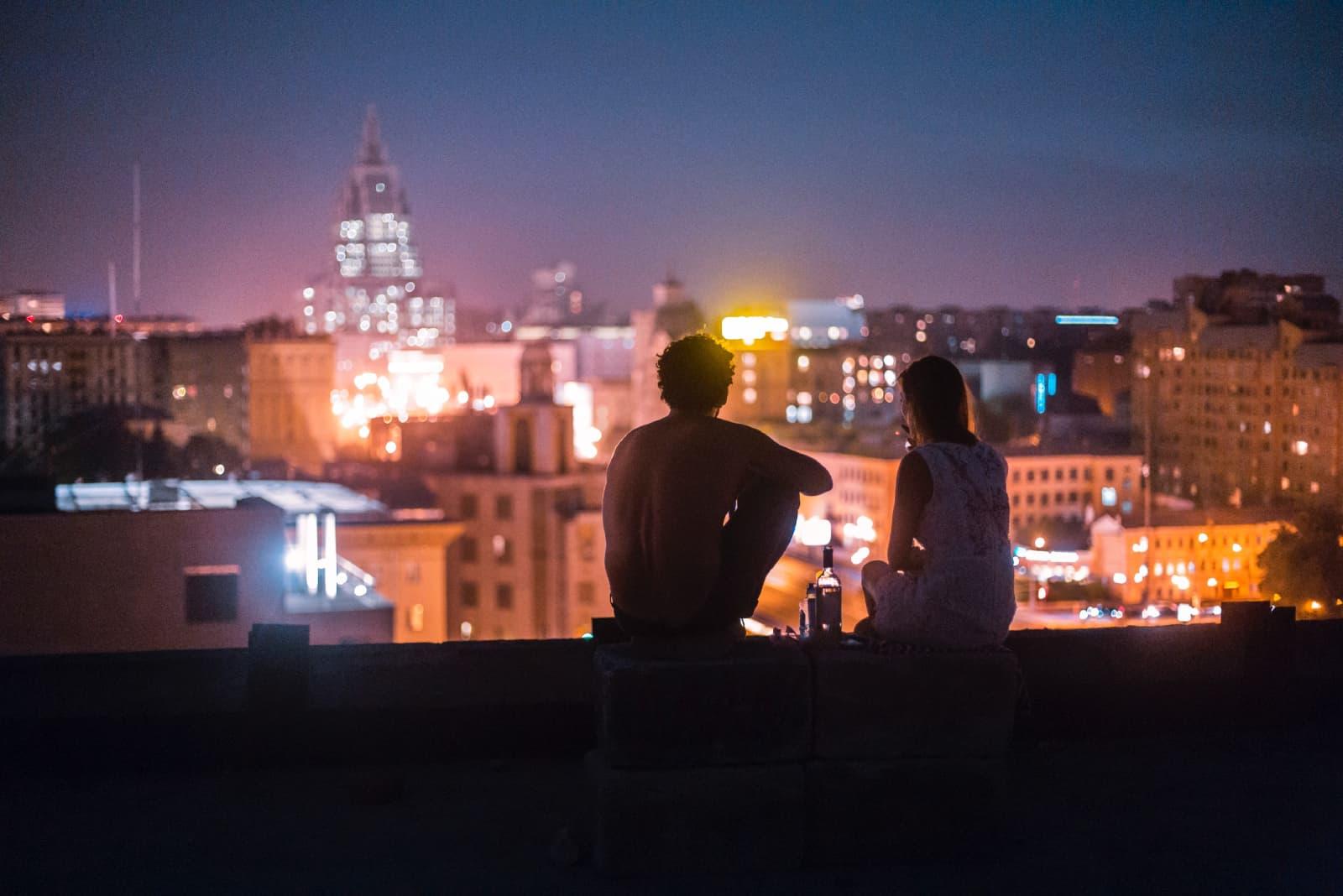 couple assis sur le toit en regardant les bâtiments